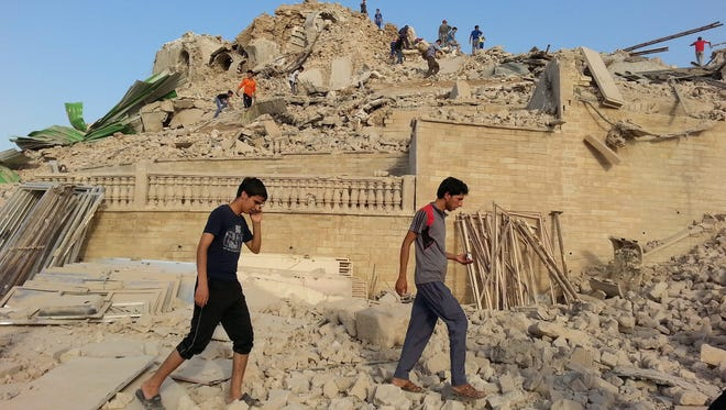 Iraqis inspect the remains of the grave of the Nebi Yunus, or prophet Jonah, in Mosul on July 24. Members of the jihadist Islamic State  allegedly demolished the historic site.