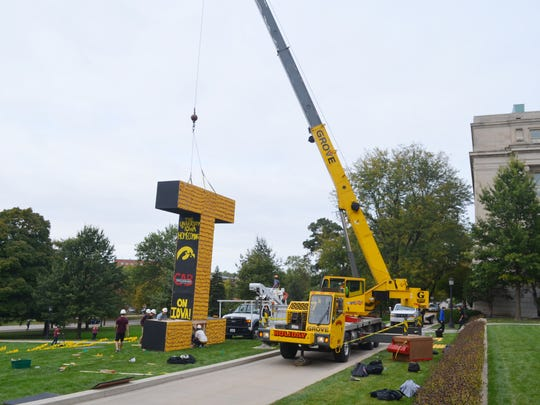 A construction crew uses a crane to erect a corn tower