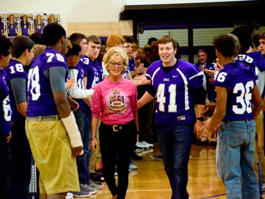 Tracy Lytle, left, and her son, Kelly, walk through lines of Fremont Ross football players at the school's homecoming pep rally Friday. Tracy and Kelly Lytle were representing their late husband and father, Rob, for the school's homecoming festivities.