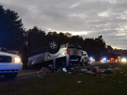 A law enforcement officer looks at an SUV that crashed after a chase Tuesday on I-240.