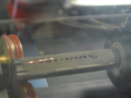 A laser engraves the handle of a whisk.
