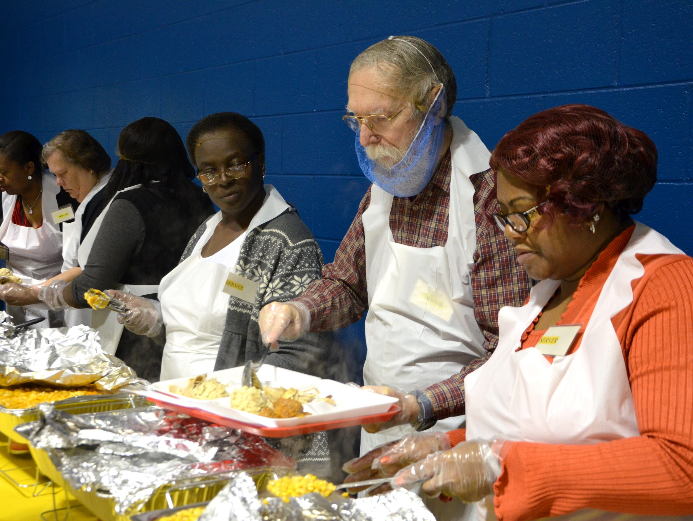 Volunteers serve food at the annual Thanksgiving dinner,