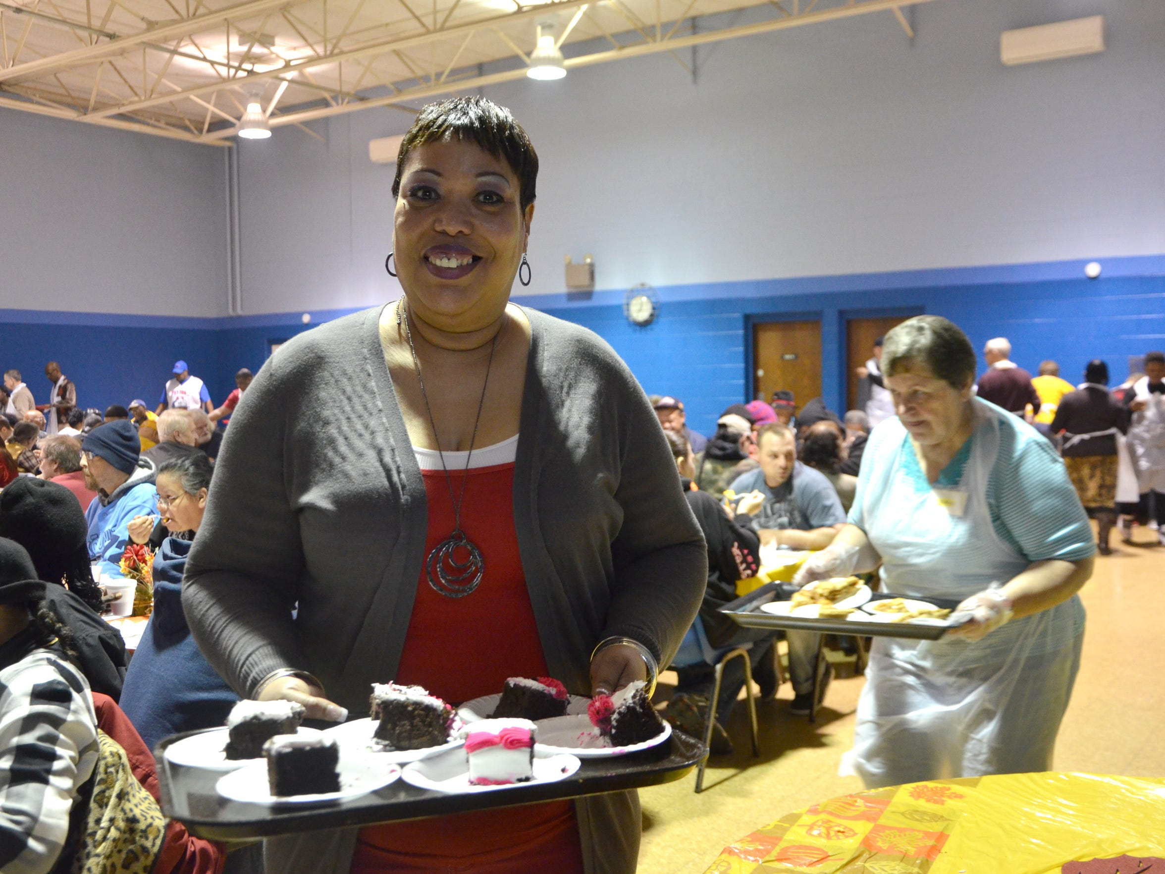 Stephanie Travis-Brown takes a tray of desserts to serve to attendees. Travis-Brown is the daughter of Lorraine Hunter, a long-time organizer of the annual Thanksgiving event.