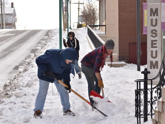 Customs House Museum employees clear the snow the old-fashioned