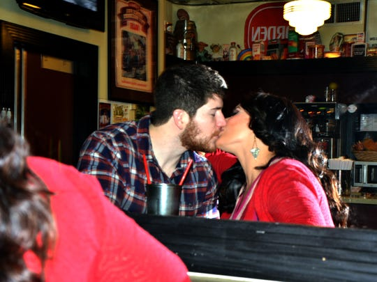 Jennifer Rausch  and Adam Clause snuggle in a booth. Heroes' journeys need best friends who ostentatiously kiss in the background.
