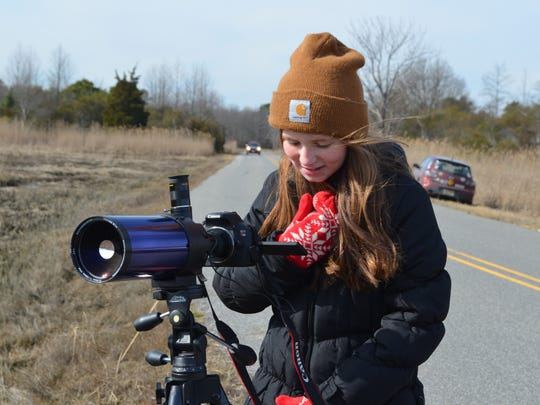 Jenna Martin, 11, of Mullica Hill, checks out an eagle on the camera screen while visiting the Maple Avenue viewing location during the Cumberland County Winter Eagle Festival on Saturday. Photo/Jodi Streahle