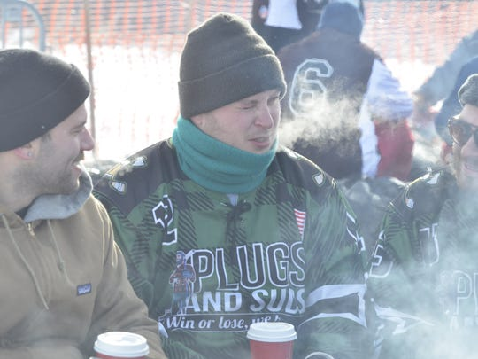 Ike Chepolis, Nathan Somerville, and Ryan Payne try to stay warm during the Pond Hockey classic in Colchester.
