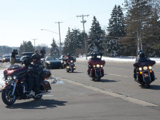 Motorcycle riders accompany the processional for funeral services for Richard and Tyler Smith Saturday. The father and son bonded over their love of working on vehicles, mourners said.