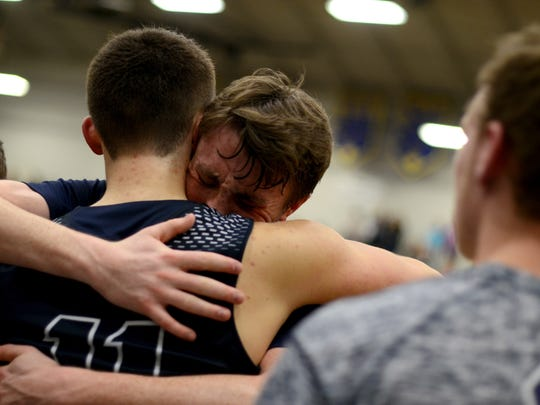 Yale senior Cody Kegley hugs a teammate after his last time on the court as a Bulldog Monday, Mar. 14, during a regional basketball game against Lake Fenton at Imlay City High School.