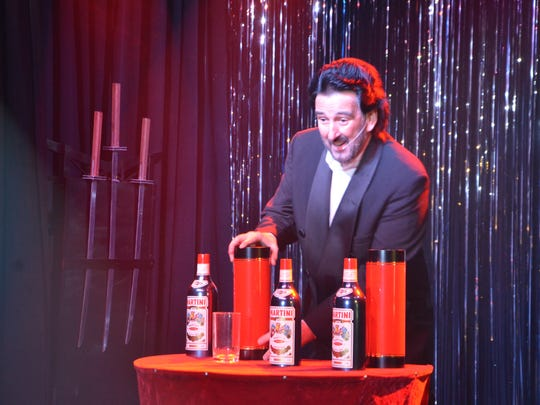 Magician John Starlini performs a trick where he produced several bottles from just two containers at Colon's 31 Flavors of Magic event Saturday.
