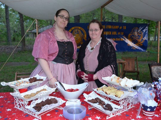 Ashley Connelly of Elmer and Viola Smithcors of Gettysburg, Penn. and formerly of Elmer, both of the Cornelia Hancock Auxiliary, served sweet treats during the Founder's Day Camp by Candlelight in Vineland. Photo/Jodi Streahle