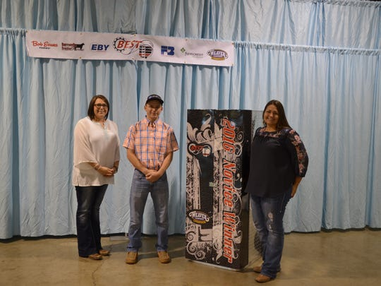 Novice participant Levi DeLong, Laurelville, Ohio won a new show box in a novice-only drawing, donated by Weaver Livestock. Pictured from left are Rachelle Vance, Weaver Leather Livestock; Levi DeLong and Angela Shoemaker, Weaver Leather Livestock.