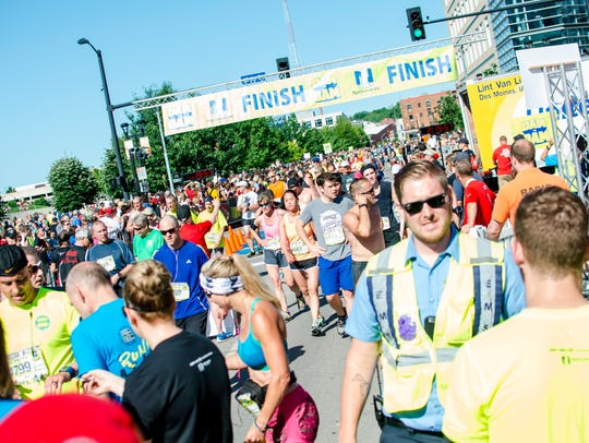 Exhausted runners crossing the finish line in downtown