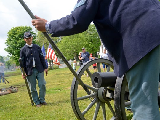 Reenactor with the 15th Michigan Volunteer Infantry, Ray Berels, watches as the cannon is tended to Sunday, June 5, during the Civil War reenactment days in Lexington.
