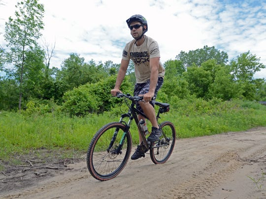Aaron Piper, of Richmond, bikes the trails Monday, June 6, at Columbus County Park.