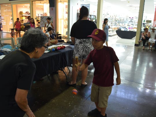 Makoa Kahele, 7, is encouraged by Guam Nikkei Association Secretary Florence Cornwell during the kendama contest preliminary round held at the Guam Premier Outlets on June 11.