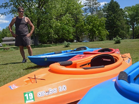 Owner Chris Trudeau with some of his kayaks for rent Monday, June 27, in Croswell.