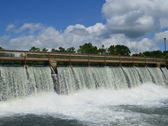 Water rushes over the dam at a rate of more than 9.7