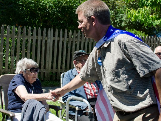 Shap Smith shakes the hand of Mary Lu Hatstat while parading in Bristol on July 4 2016