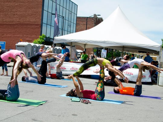 A group of acro yoga performers doing a routine in