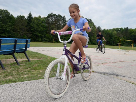 "Myiah Brown, 9, of Port Huron, rides her bike with her dad, Jordan Brown, as they search for Pokemon with the new ""Pokemon Go"" app Monday, July 11, behind Michigamme Elementary."