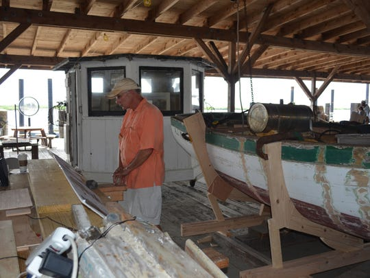 """Leo Warner of Vineland, a volunteer at the Bayshore Center at Bivalve, looks at the new Cashier Pilot House exhibit during Maritime Heritage Day at the Bayshore Center at Bivalve on Saturday. The exhibit includes the pilot house from the 150-year-old """"Cashier."""" The pilot house was added after the sails were removed from the ship. Photo/Jodi Streahle"""