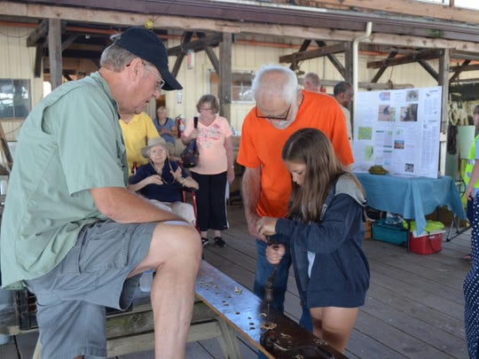 Sarah Reina, 9, of Northfield uses a bit and brace to drill a hole in a plank of wood at the Bayshore Center at Bivalve during Maritime Heritage Day. Also pictured are Paul Hettinger of Glassboro, a Bayshore Center volunteer, left, and Nick Reina of Millville, center. Photo/Jodi Streahle