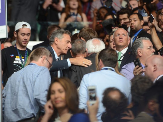 Vermont Gov. Peter Shumlin pats the back of Sen. Bernie Sanders after Sanders called for all Democratic National Convention delegate votes to go to Hillary Clinton on Tuesday, July 26, 2016. Shumlin was a superdelegate at the convention who supported Clinton.