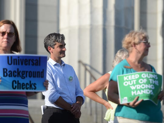 """Burlington Mayor Miro Weinberger, center, listens to a rally for universal background checks on gun sales at the Statehouse in Montpelier on Thursday. Weinberger said support for the measure indicated a """"new day"""" in Vermont politics."""