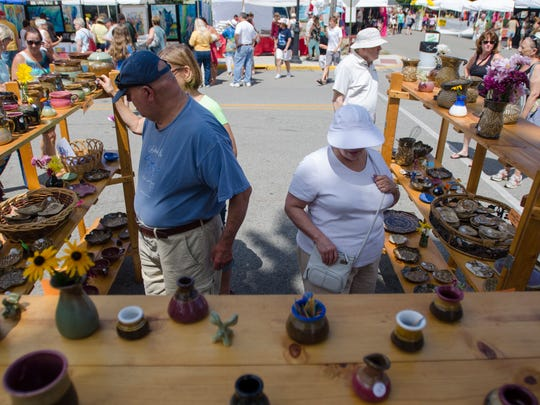 People check out pottery on display, Sunday, Aug 7,
