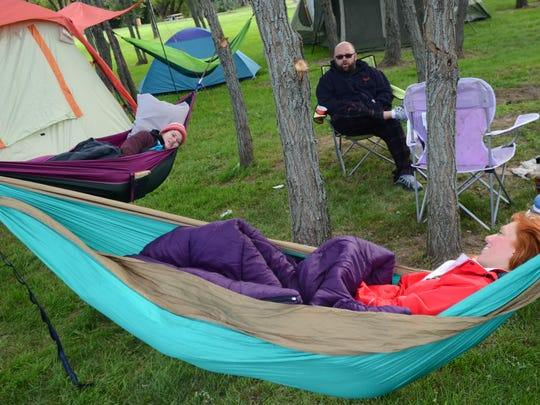 NICOLE HAYDEN/TIMES HERALD Paddle and Pour wrapped up Sunday after a cold weekend of kayaking and camping. Danielle Reid, 25, Ben Krenke, 37, and Jordan Owen, 23, hang out Sunday morning in 2015 as they wait for the Slow Paddle to start.