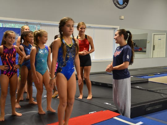 Savannah Thompson, former Olympian and owner of Hangtime Gymnastics, encourages members of her competition team during a class on August 11, 2016.