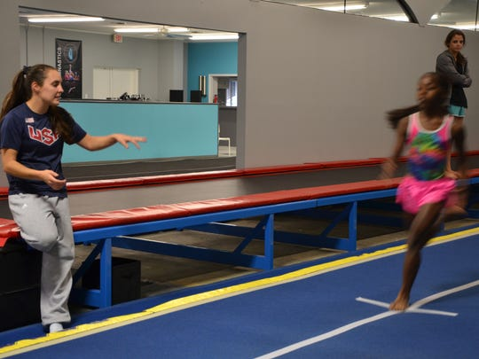 Savannah Thompson, former Olympian and owner of Hangtime Gymnastics, instructs a member of her competition team during a class on August 11, 2016.