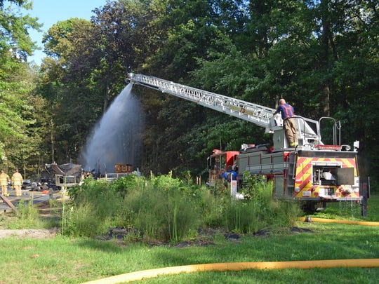 Firefighters from Pemberville Freedom Fire Department's Ladder Truck No. 5 pour water on the embers after a barn fire Thursday afternoon in Woodville Township.