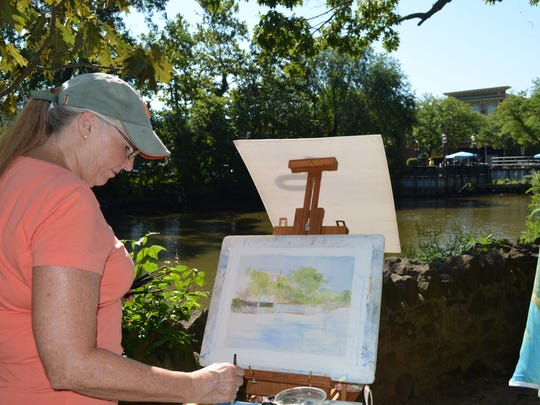 Yvonne Pecor Mucci of Verga works on her Plein-Air entry along the Cohansey River bank in Bridgeton. Photo/Jodi Streahle