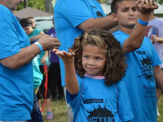 Brooklynn Rescinito, 6, of Clayton releases a butterfly during the opening ceremonies of the 2016 Bill Bottino Mud Run for Cancer at the Cumberland County Fairgrounds on Saturday. Photo/Jodi Streahle