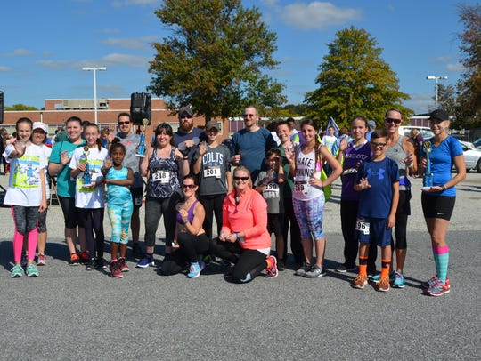Robot Run 5k winners pose for a photo with their awards.