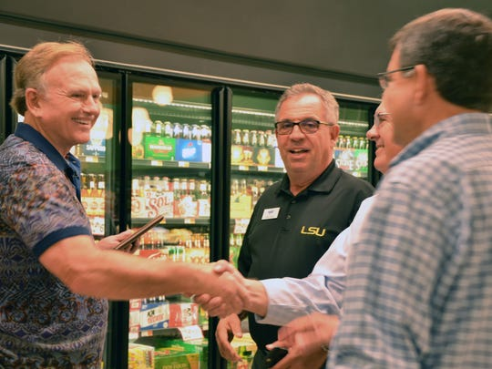 Greg Champagne, owner of Champagne's Market, accepts an award Oct. 19 from Associated Grocers' representatives Tony Fatta, Doug Weltz and Brian Bernard in recognition of being a 30-year veteran Associated Grocer.