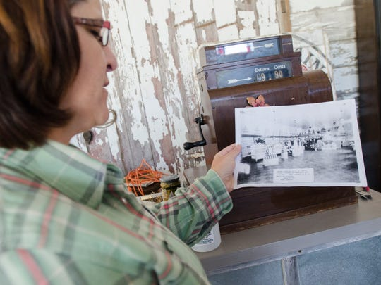 2thirty5 owner Dawn Neagos shows an old photograph of her building Sunday, Oct. 23, in Marine City.