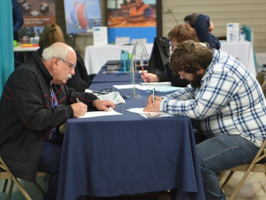 In this file photo, job seekers fill out applications