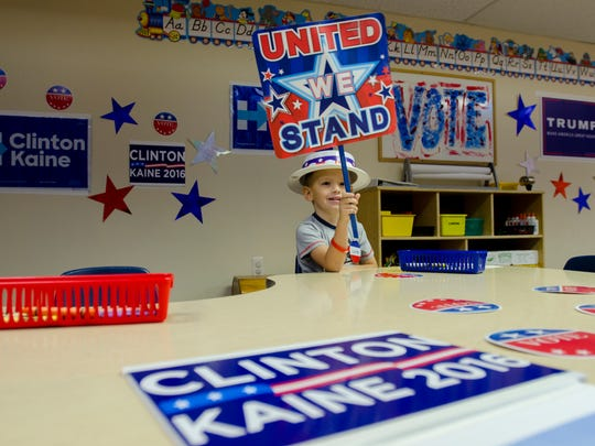Carter Moyer waves his poster Monday, Nov. 7, during an election day ice cream party at the Marysville Children's Center.