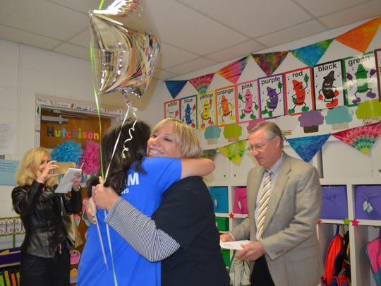 Ben Milam Elementary School teacher Tiffany Hutchison (center right) gets a hug from Principal Ana Griffiths after receiving her Wichita Falls ISD Foundation IDEA grant from Lance Spruiell, president of the foundation board (right).