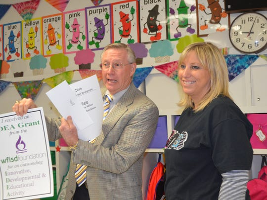 Tiffany Hutchison, a teacher at Ben Milam Elementary School, receives a surprise Nov. 18 from Lance Spruiell, board president of the Wichita Falls ISD Foundation. She and fellow Milam teacher Amanda Miller learned they are IDEA grant winners. They will use their grant money to fund an iPad accessory called an Osmo.