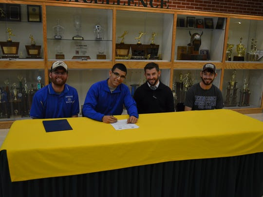 Northwest's Antoino Alejos (second from left) signs