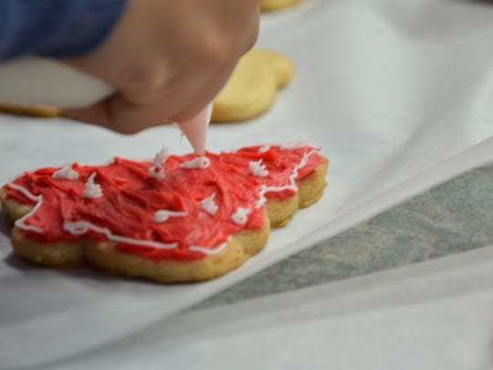 Academy of the Sacred Heart Boarders decorate cookies they baked for Mona's Munchies as part of a service project on Saturday, December 10, 2016.
