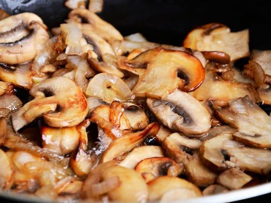 sliced mushrooms stir-fried in a pan. close-up full frame