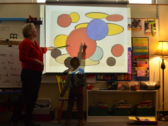 Bonfils shows Judy Klima what he sees in Emily Stewarts' class at Integrated Arts Academy at H.O. Wheeler on Jan. 3, 2017.