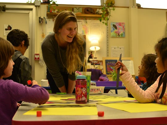 Emily Stewart, a kindergarten teacher at the Integrated Arts Academy helps her students with their art project on Jan. 3, 2017.