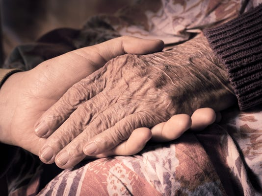 girl's hand holds an old woman's hands