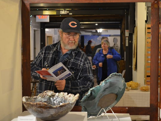 Lester Cramer of Millville admires his wife's pottery